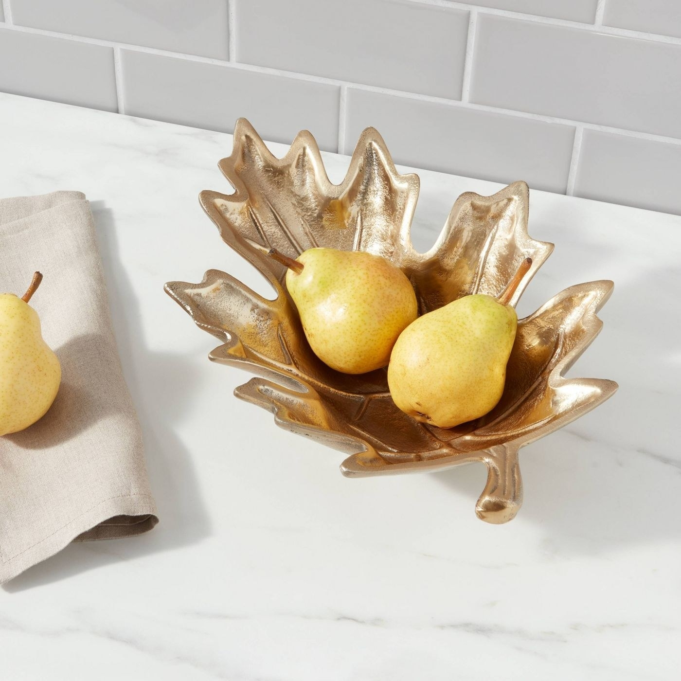 the gold leaf serving tray with two pears inside