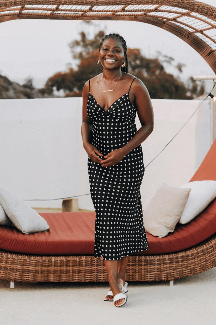 model wearing black and white polka-dot midi dress