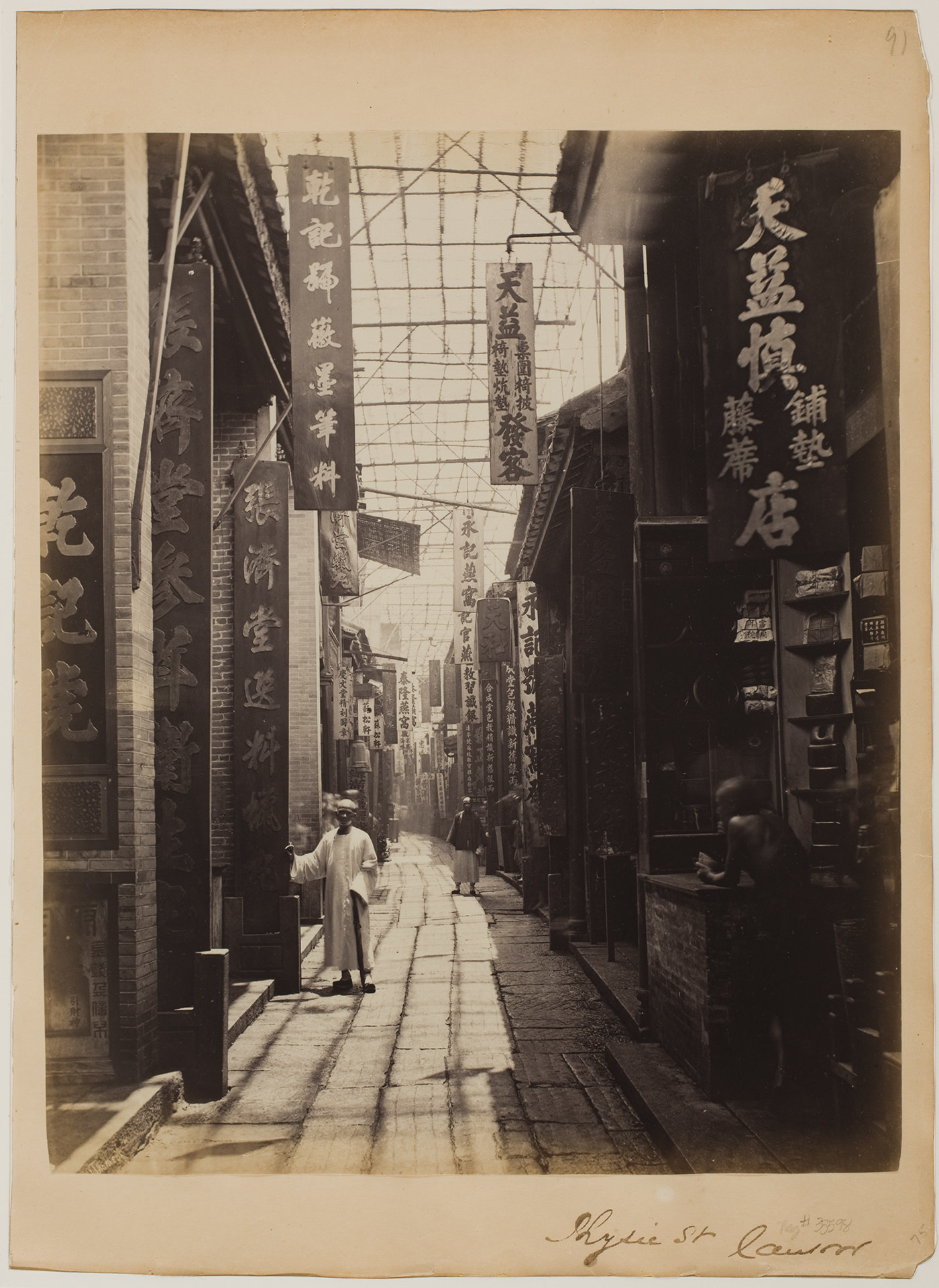 A man stands near a doorway in China near two other men, one standing in shadows, on an otherwise empty street of storefronts