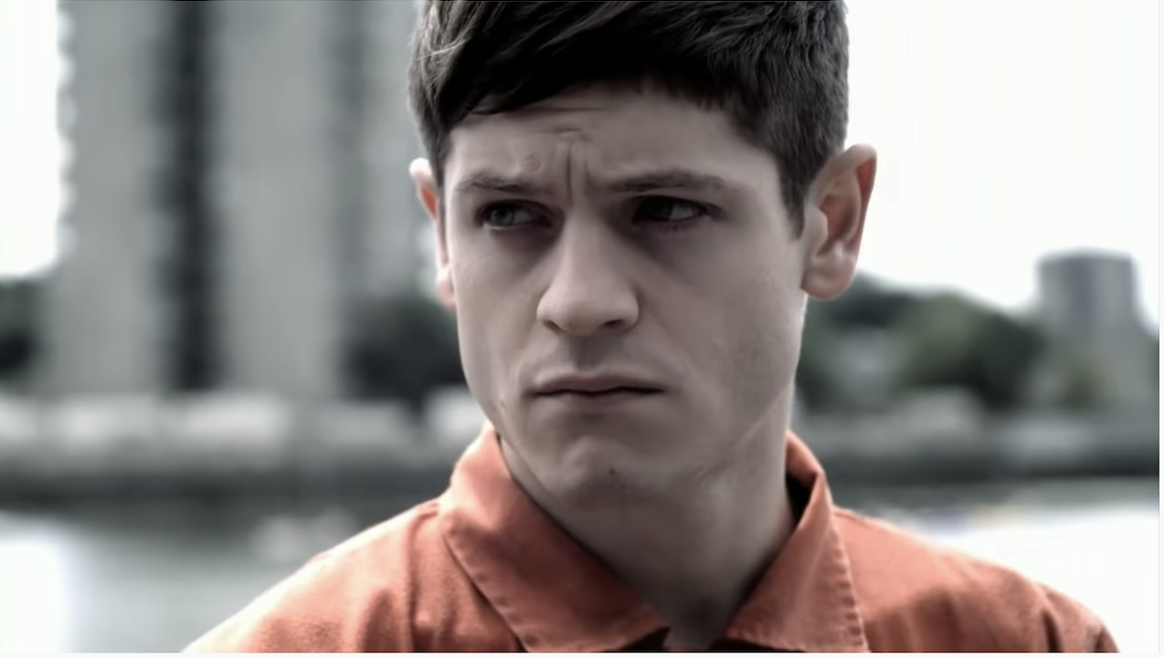 Simon in the orange jumpsuit in the first episode