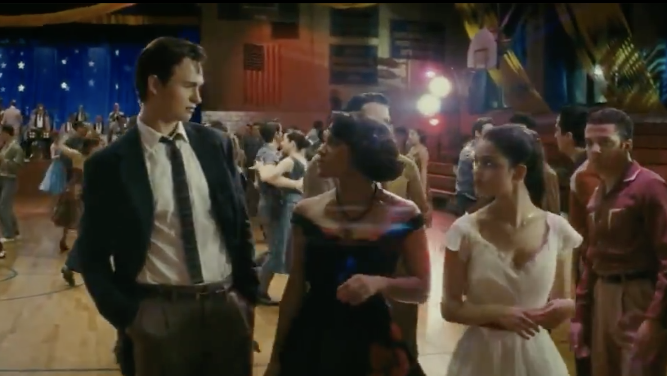 Ansel's character standing next to Maria and another woman at a dance