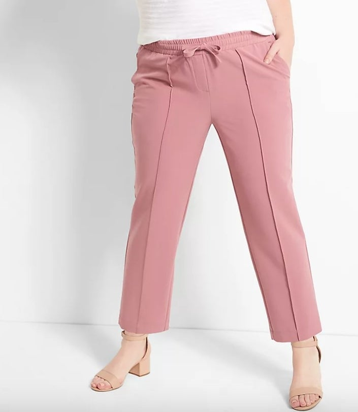 Model wearing pink pants and white top and nude shoes