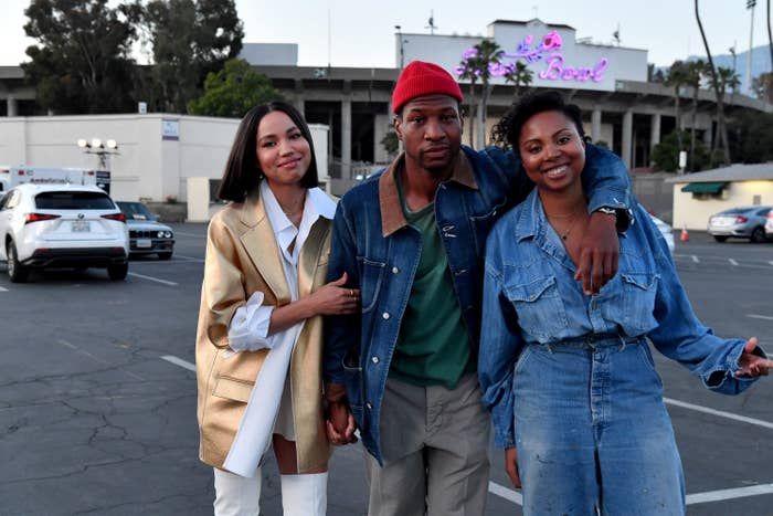 Jurnee, Jonathan Majors, and Misha Green taking a photo in a parking lot