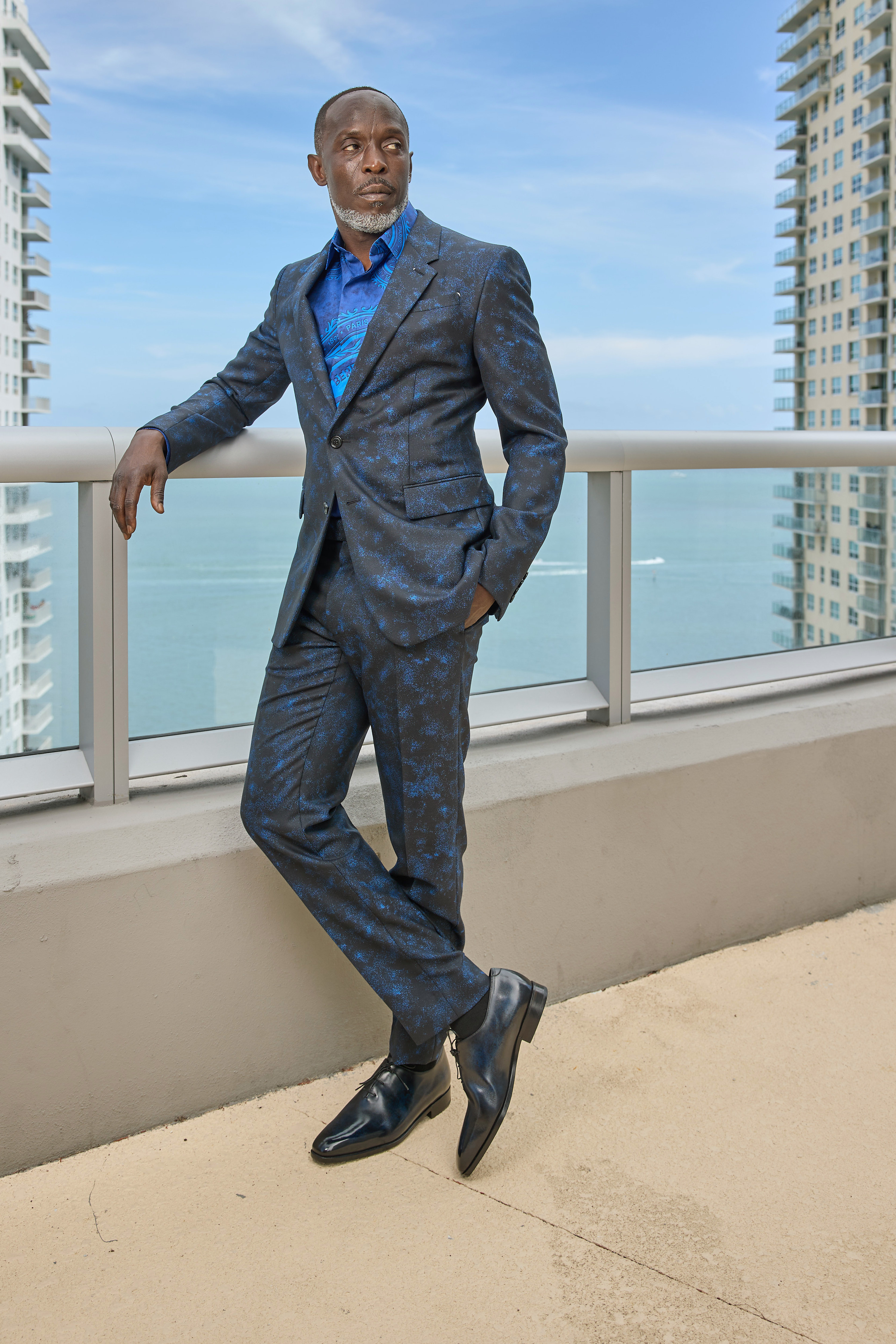Michael wears a suit as he leans against a railing for a photo