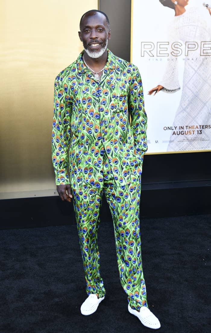 Michael K. Williams smiling while on the red carpet of an event as he poses in a peacock feather print shirt and pants