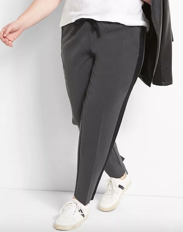 Model wearing grey and black pants with a white top and black jacket
