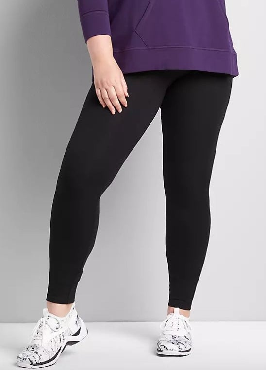 Model wearing black leggings with purple top and white shoes