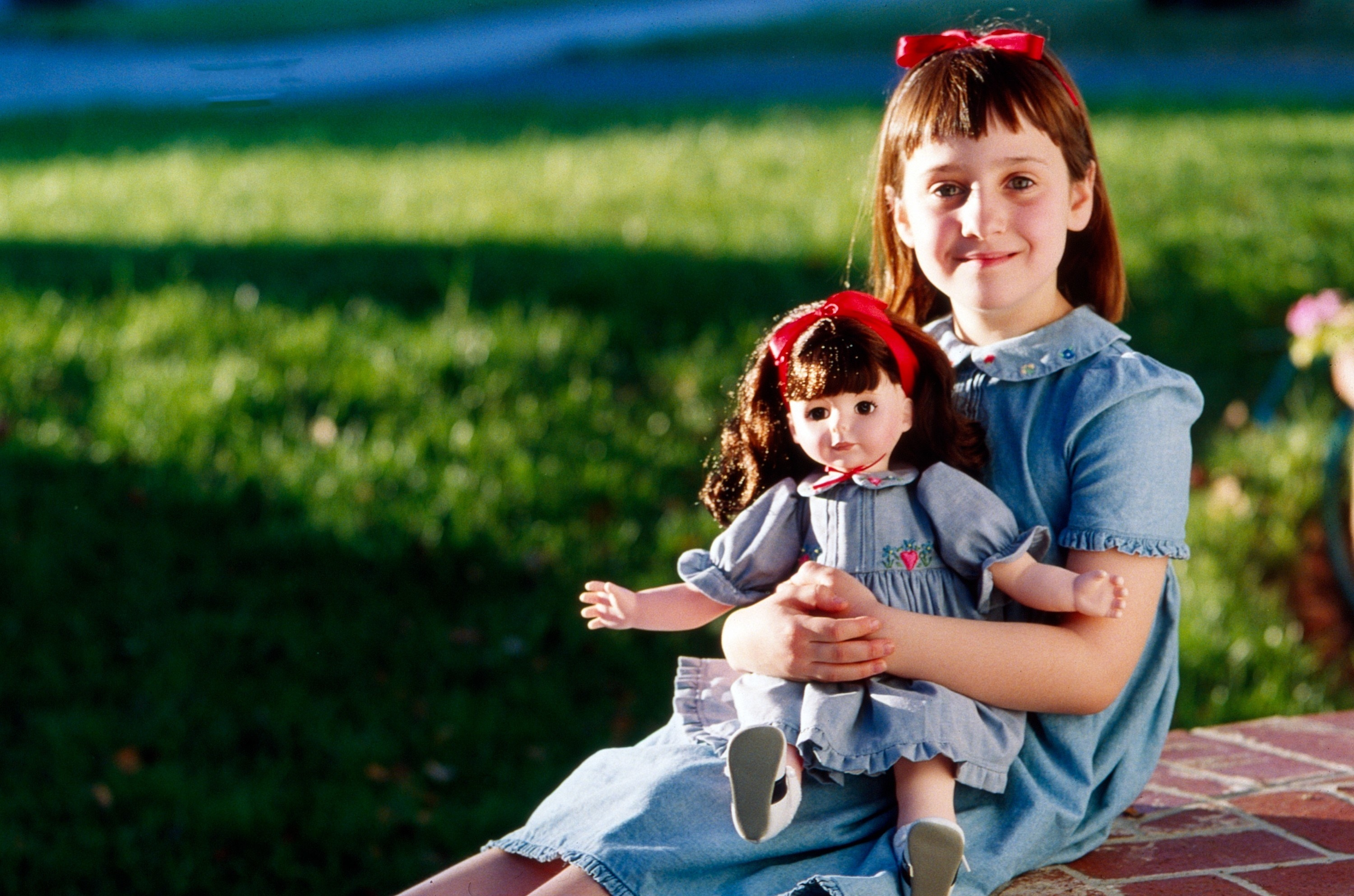 Matilda holding a doll that is dressed like her