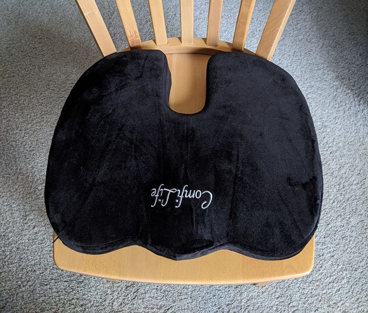 The black u-shaped cushion on a wooden chair