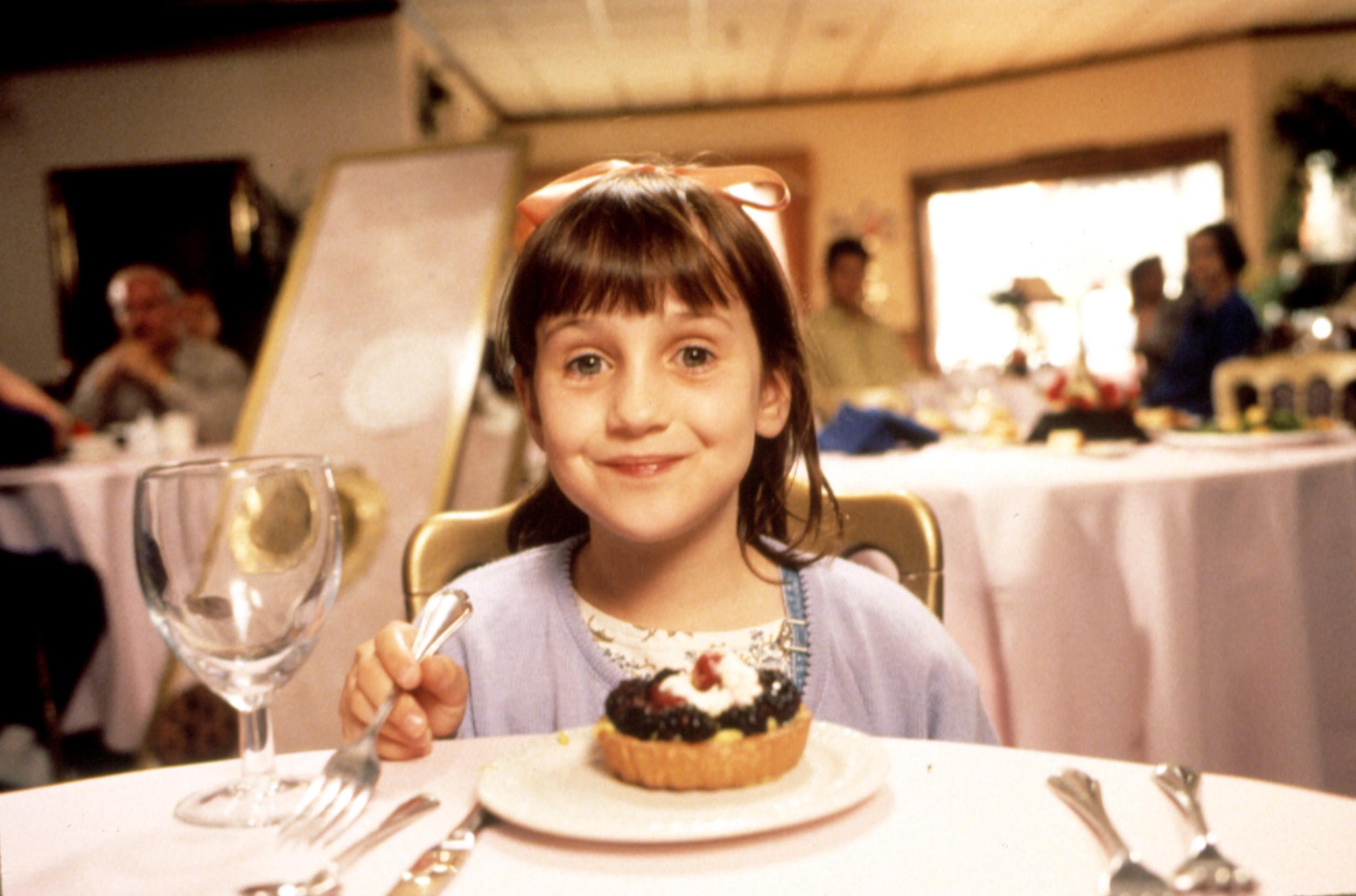 Mara Wilson as Matilda, eating a fruit tart at a restaurant
