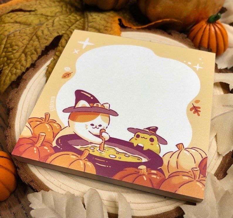 the notepad which has an illustration of a cat and a toad stirring a cauldron