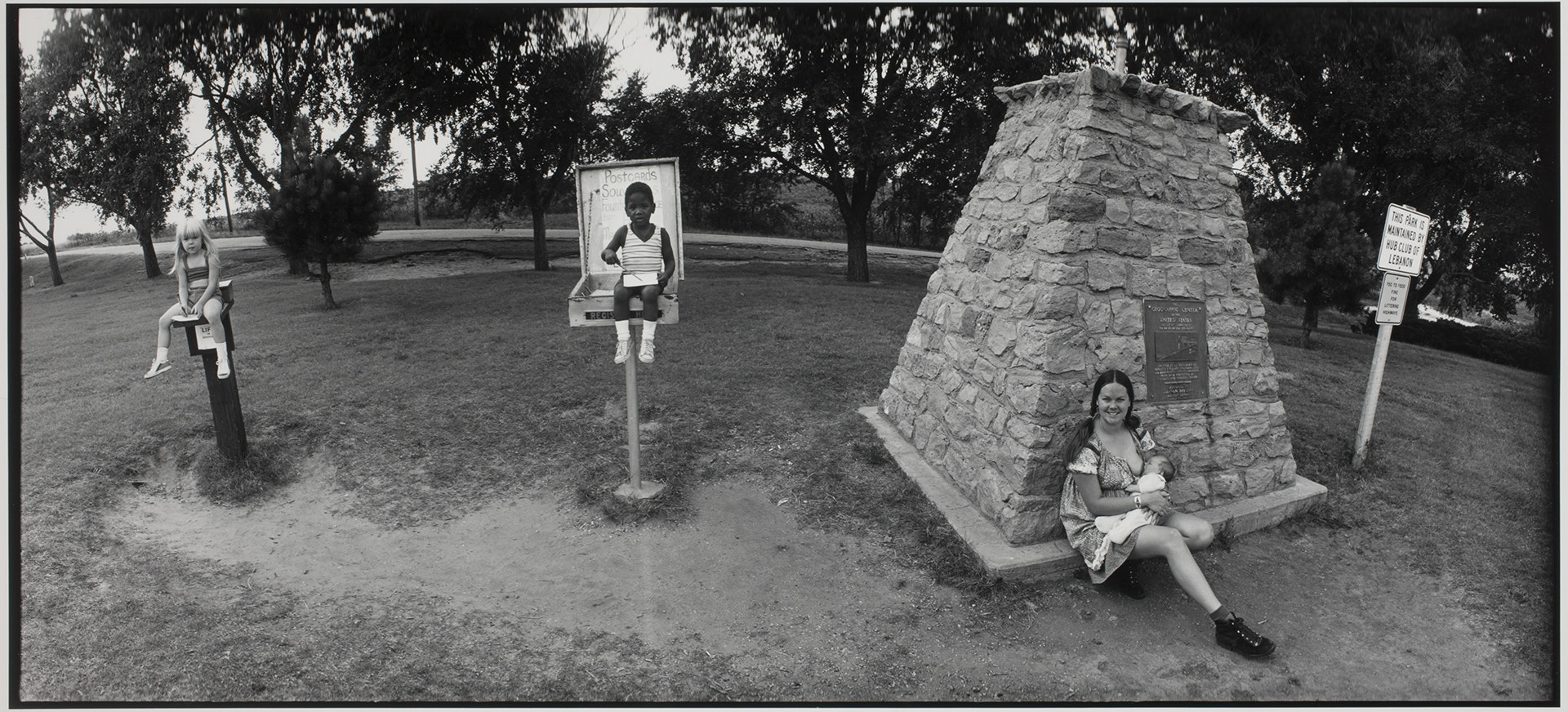 A child sitting on a water fountain, a child sitting on a raised platform, and a smiling woman leaning against a monument and nursing a baby