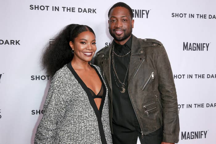 Gabrielle and Dwyane smiling as they pose on a red carpet together