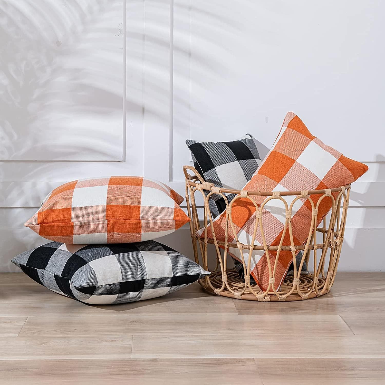 four throw pillows in orange and black plaid