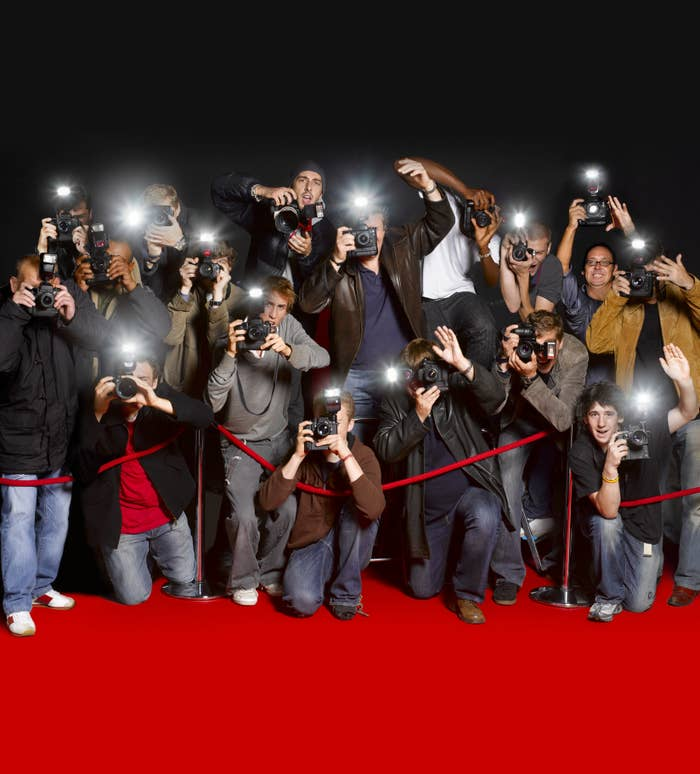 stock photo of paparazzi preparing to take photos on a red carpet