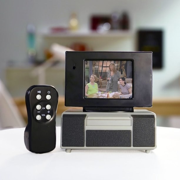 """Mini television and remote on white table in home with """"Friends"""" playing on it"""