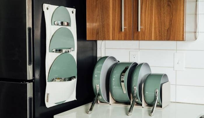 the green pan set in the organizing system on the counter top, with the lid organizer attached to the side of a fridge