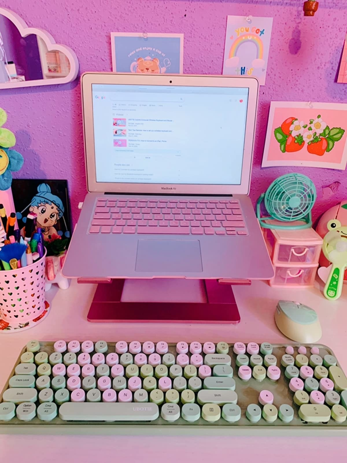 pink and green raised keyboard below pink laptop on colorful desk