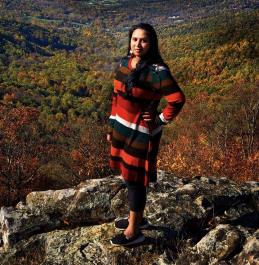 a reviewer wearing the multicolored striped dress in front of autumnal forest