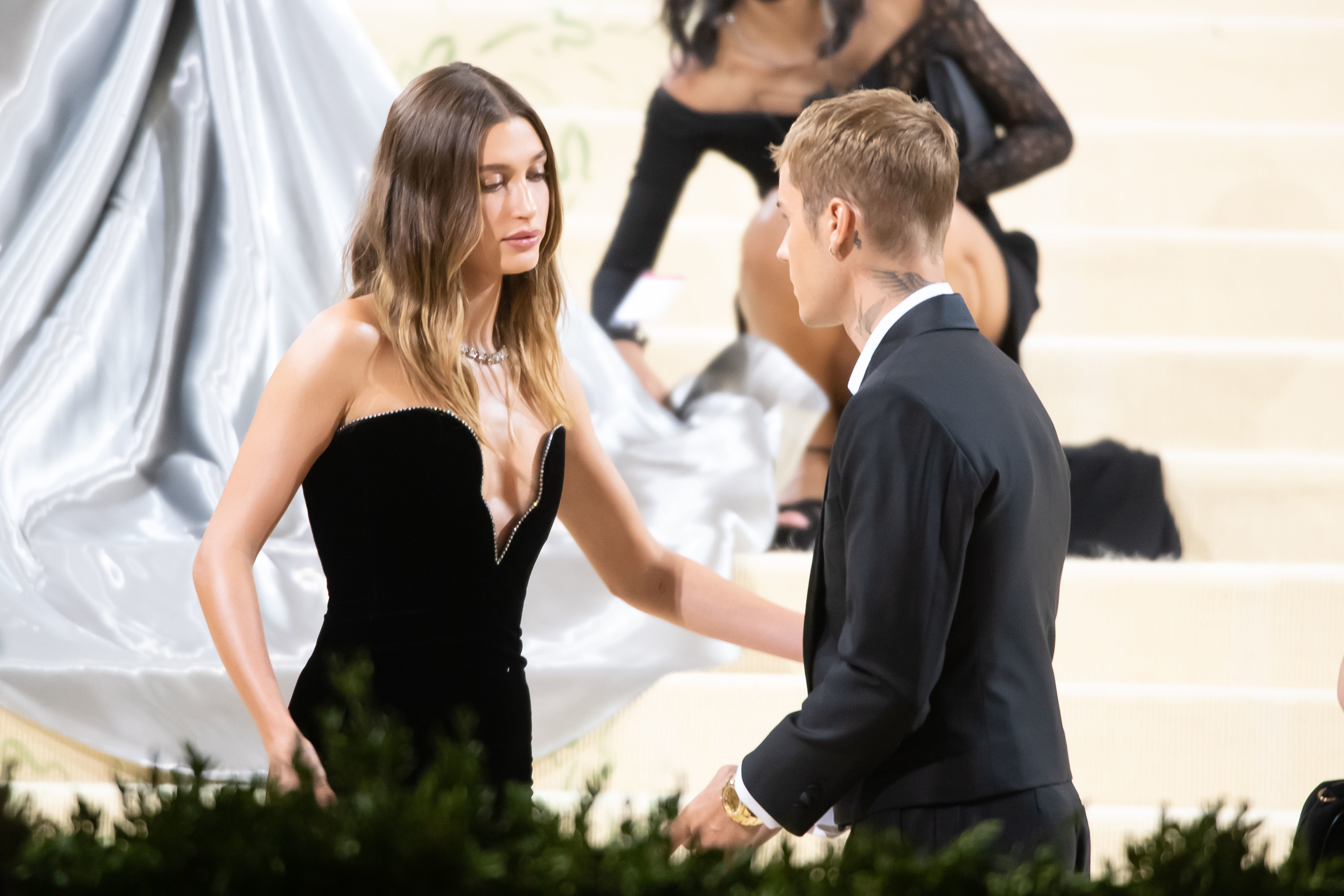Hailey reaches out for Justin while he looks over at her while walking the carpet