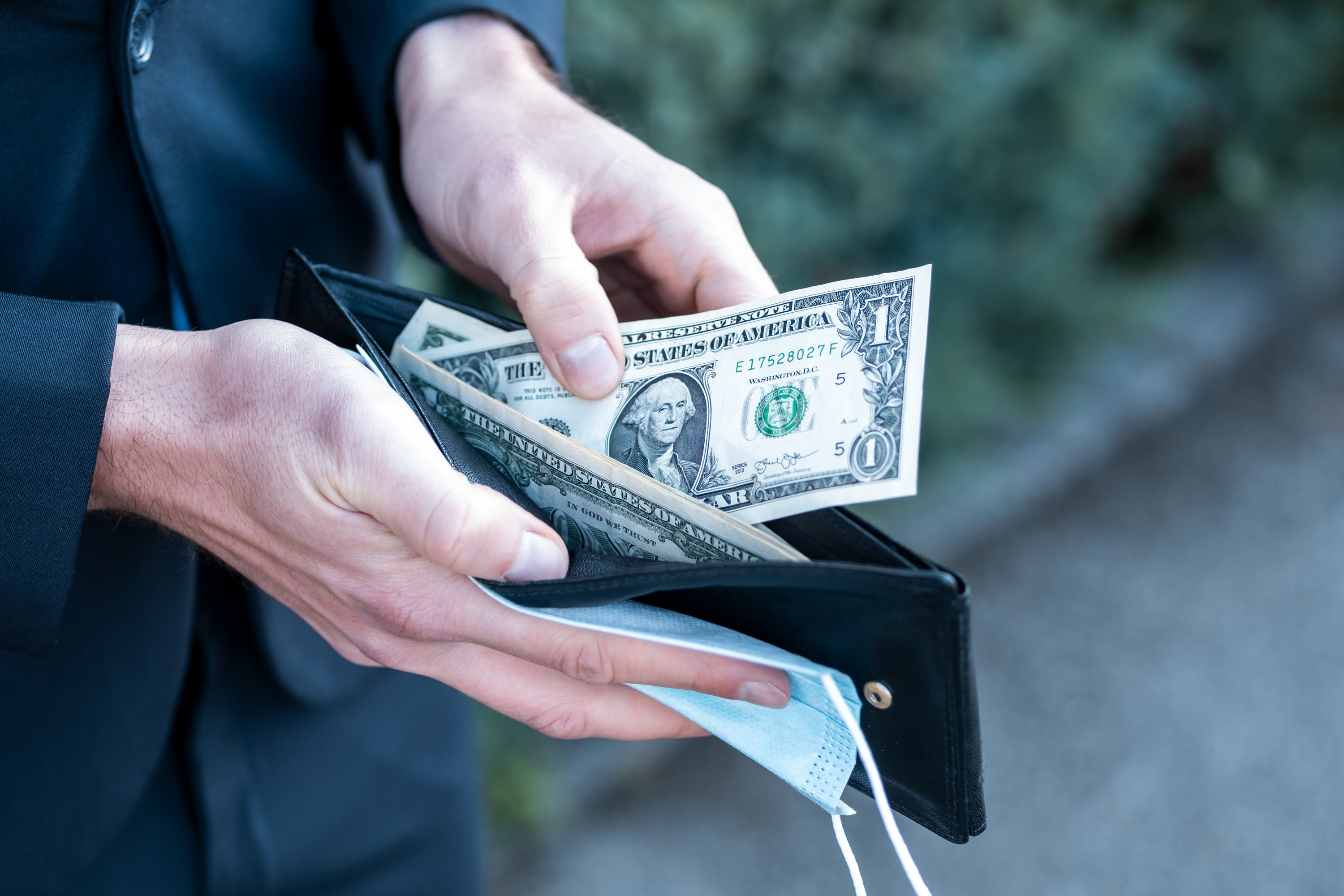 Person taking cash out of their wallet