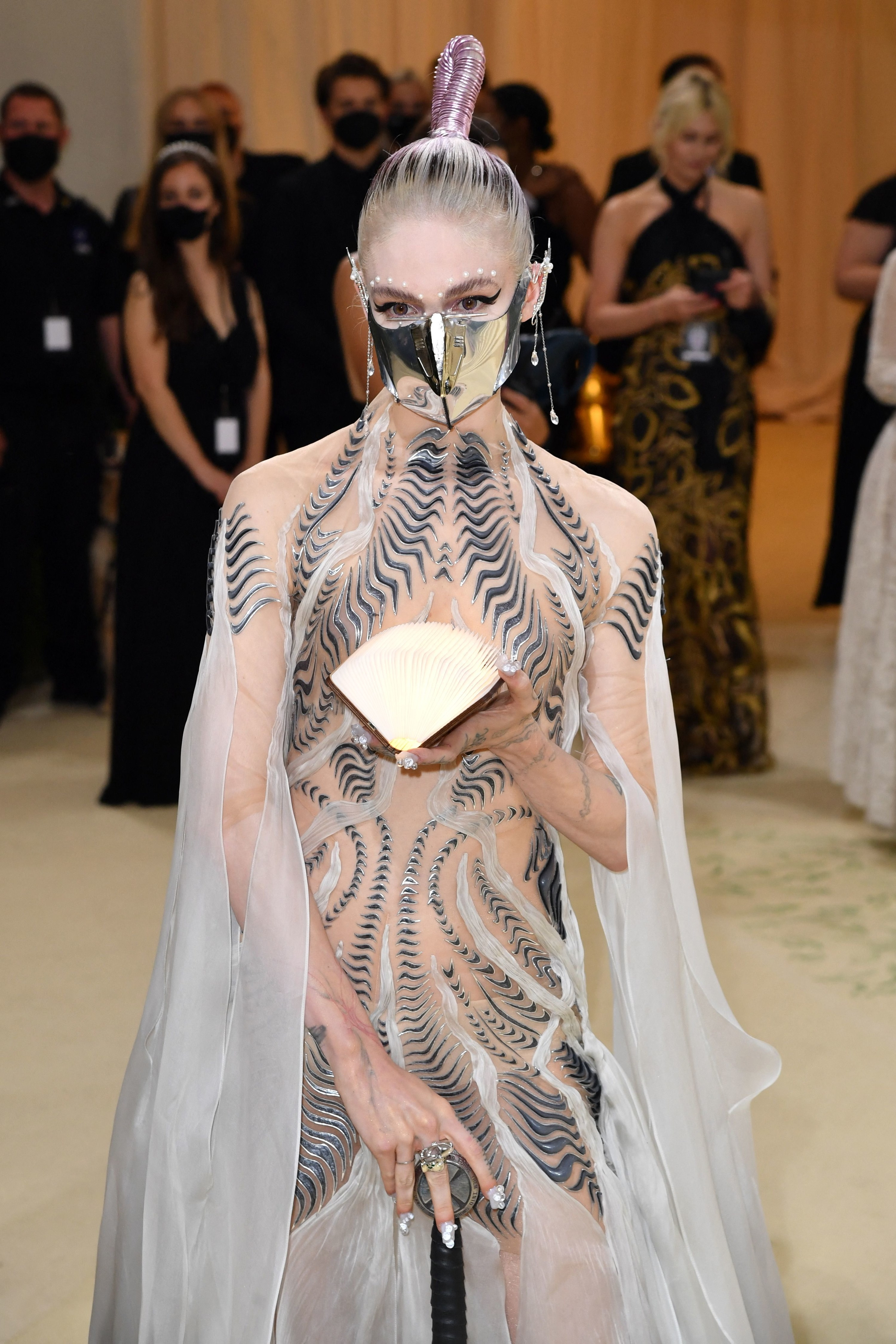 Grimes holds an open book on the carpet