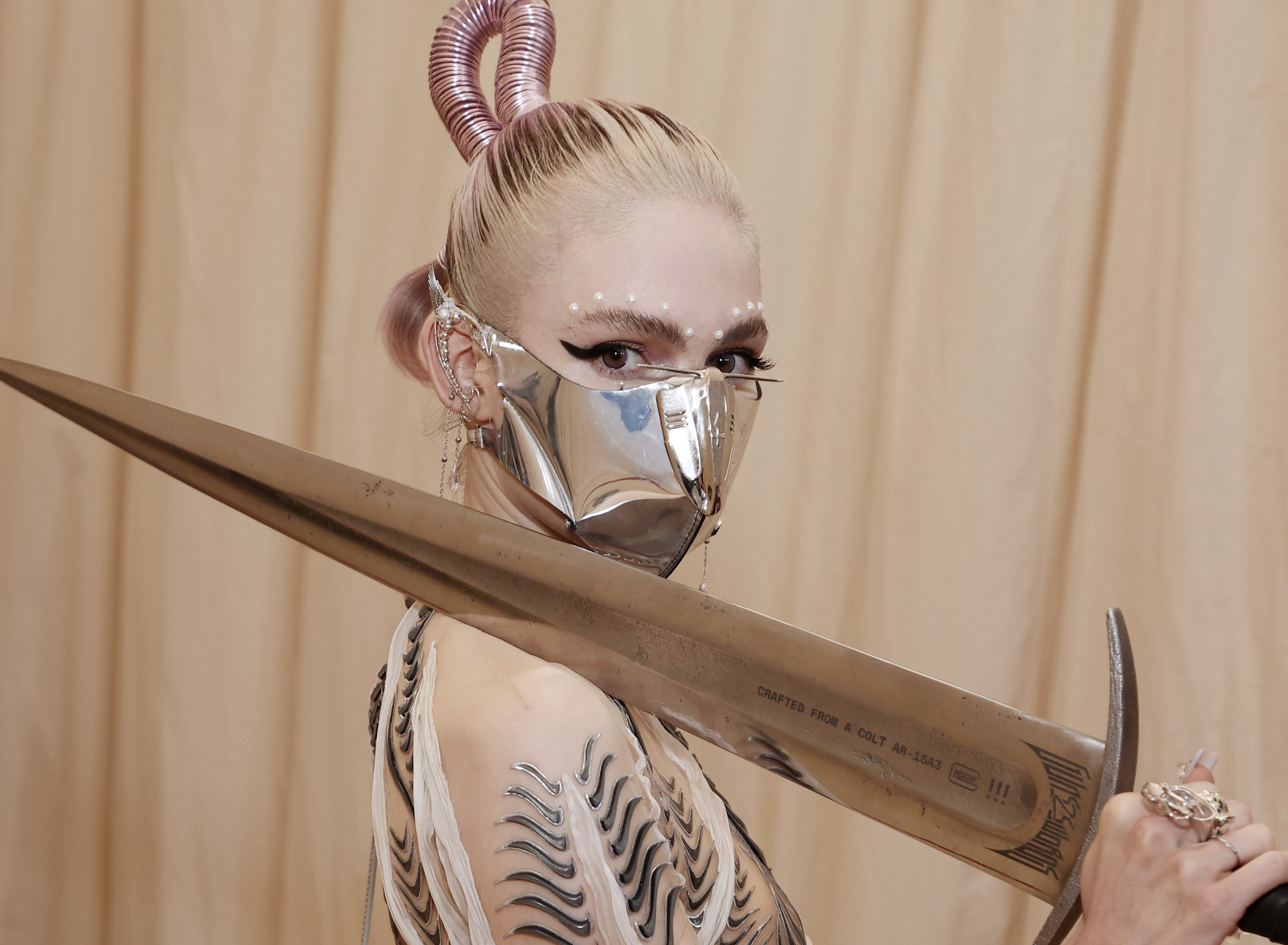 Grimes holds the sword, leaning it on her shoulder