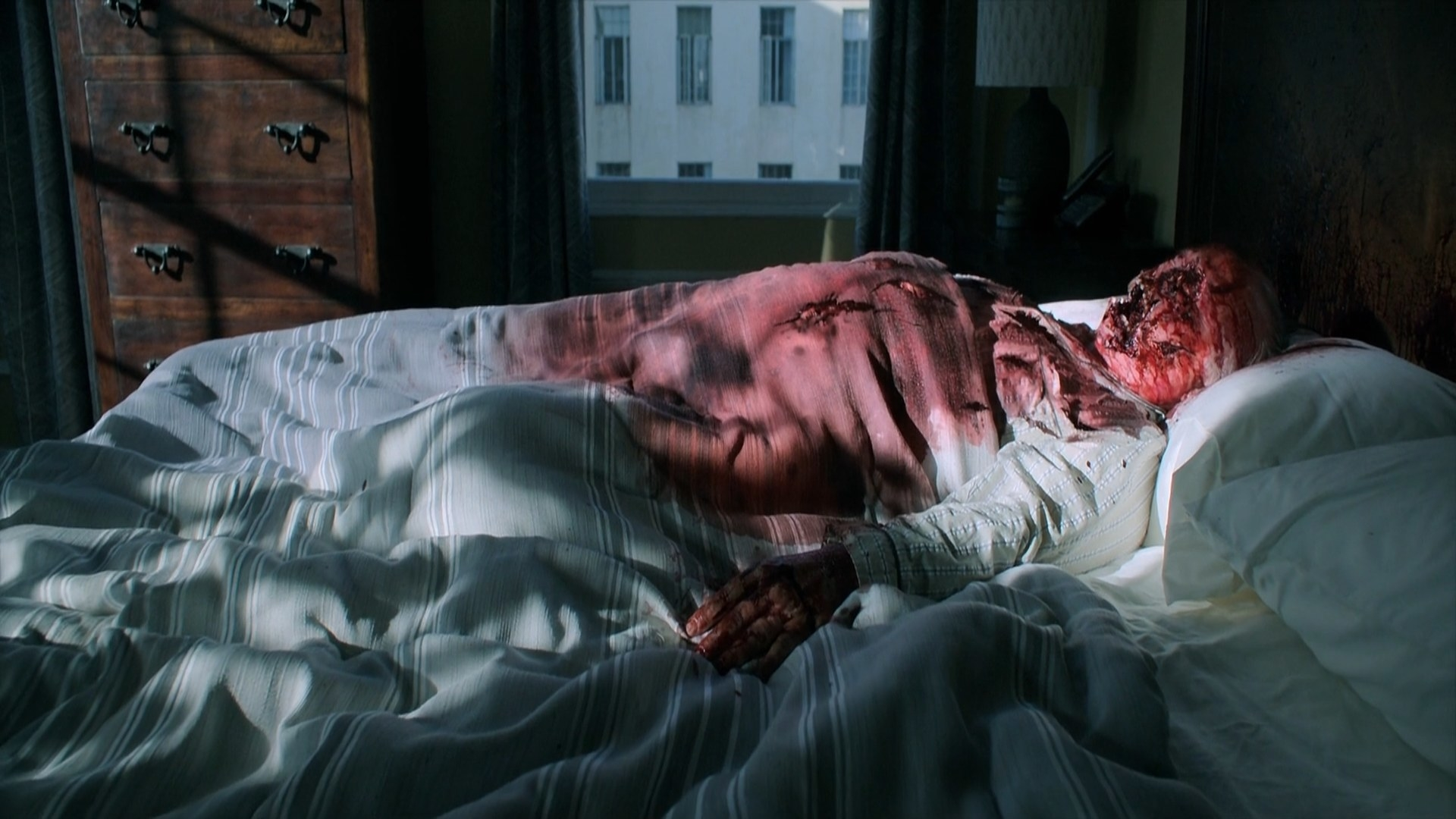 A dead man with his face stabbed lying on bed.
