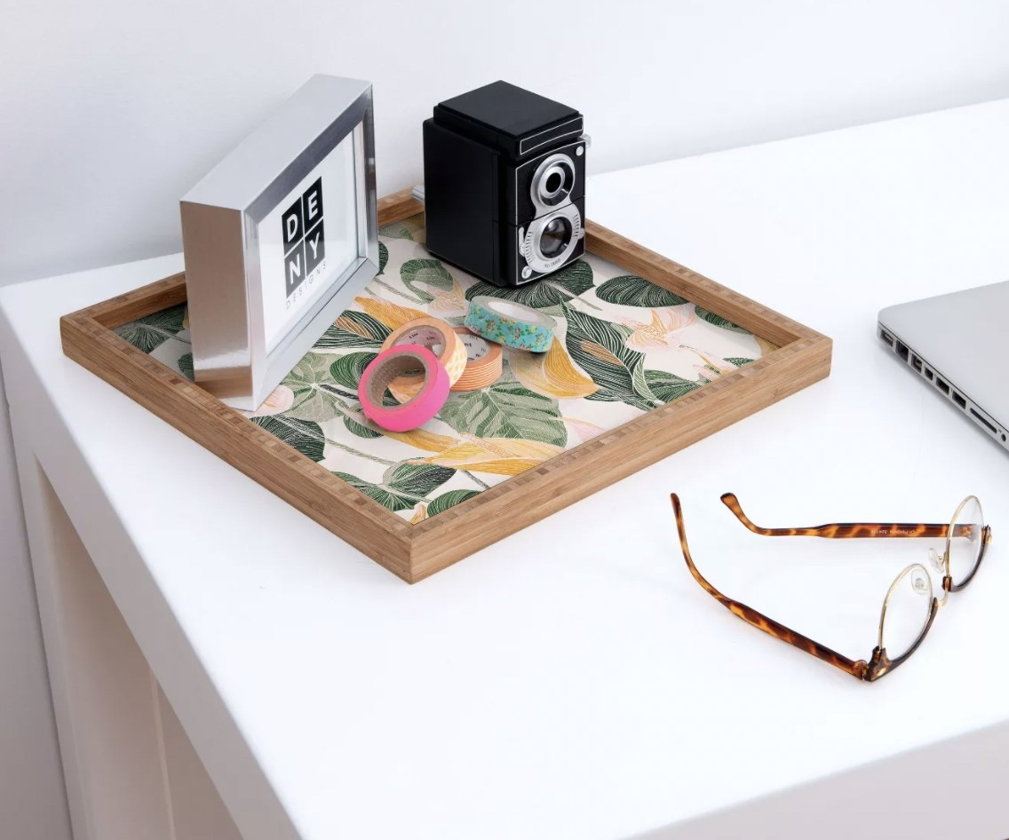 a square bamboo tray with leaves printed on the inside