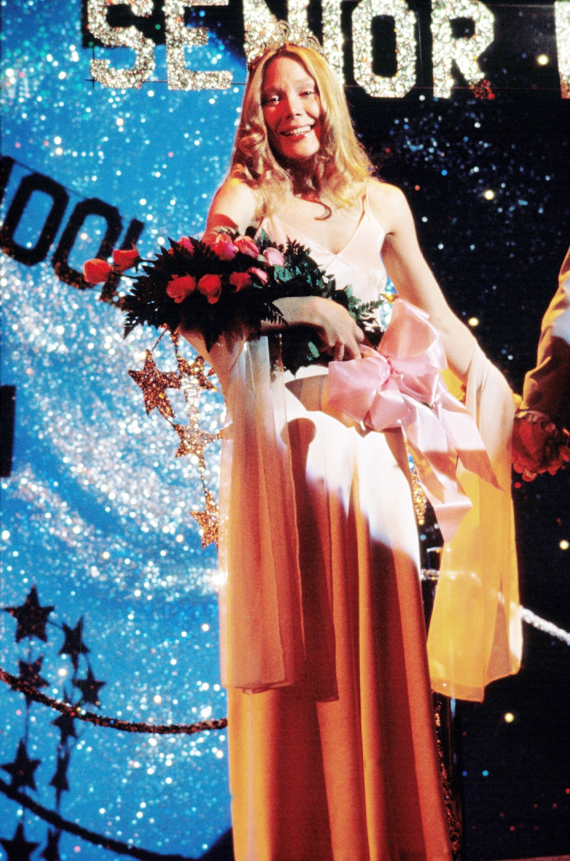 Carrie receiving flowers and a crown in a long pink dress