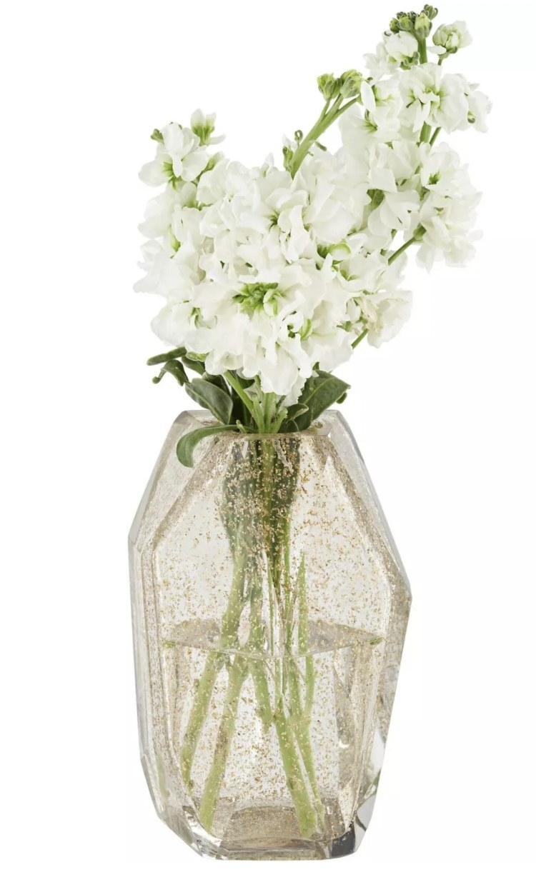 a smoked glass vase with gold glitter inside holding flowers