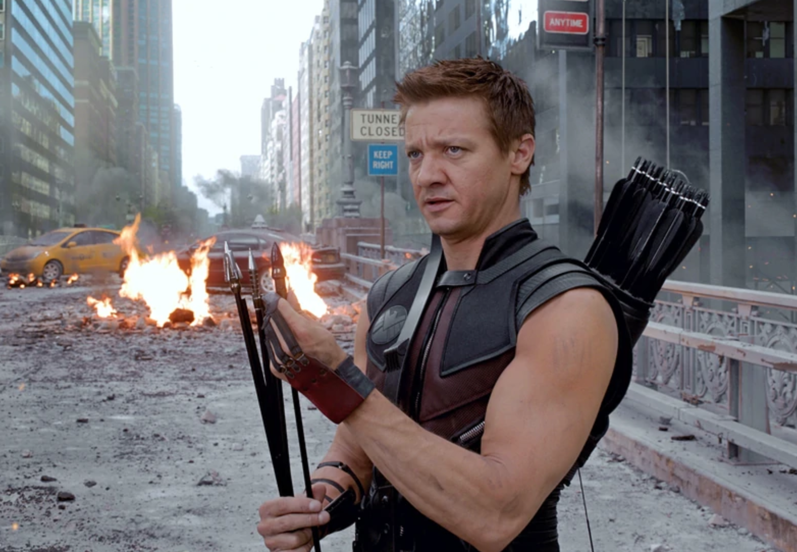 Hawkeye stands in front of a raging fire while fixing the tips of his arrows