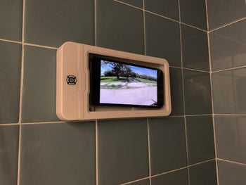 Reviewer photo of the shower mount with a phone inside playing a video