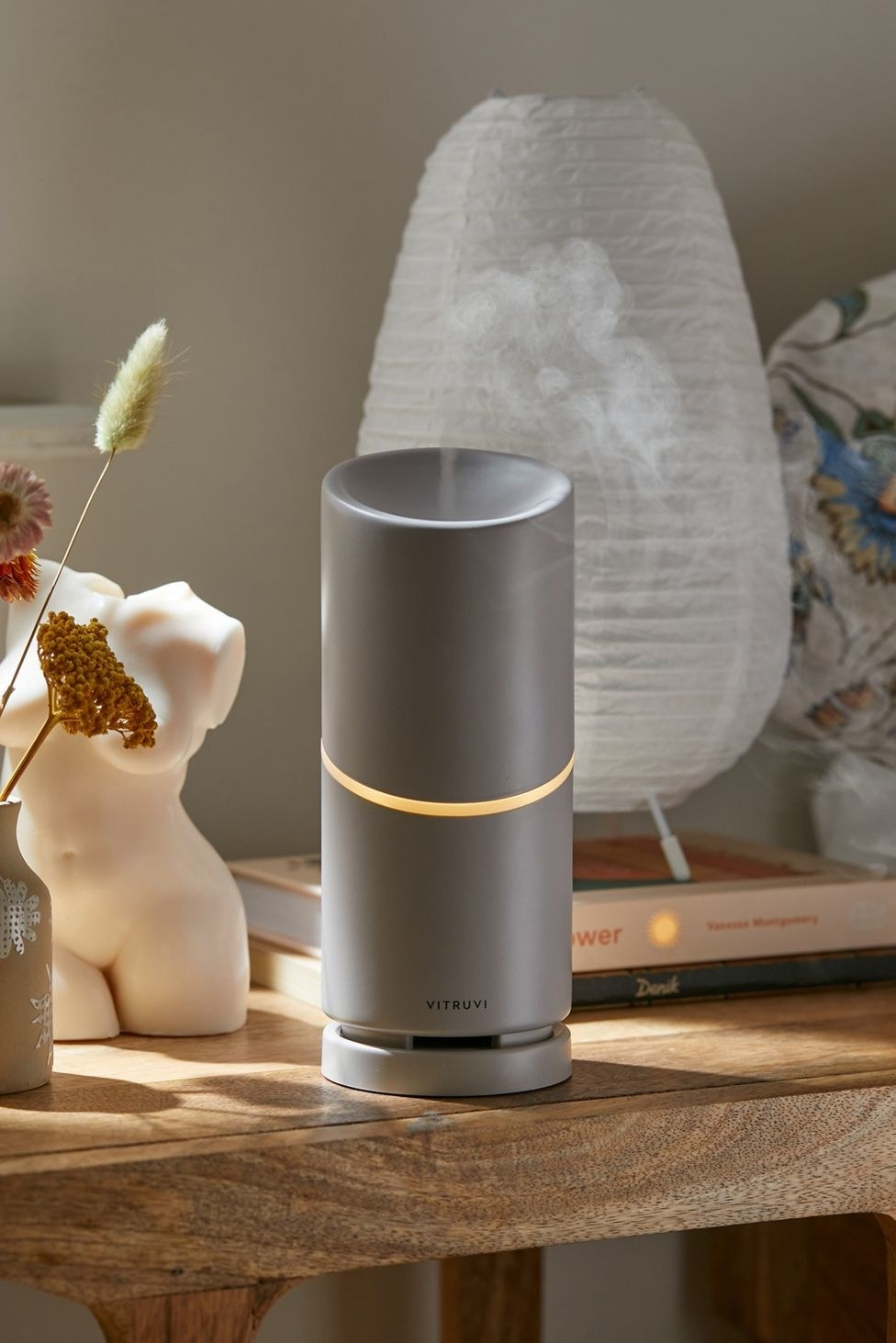the light grey Vitruvi Move cordless diffuser on a wooden table