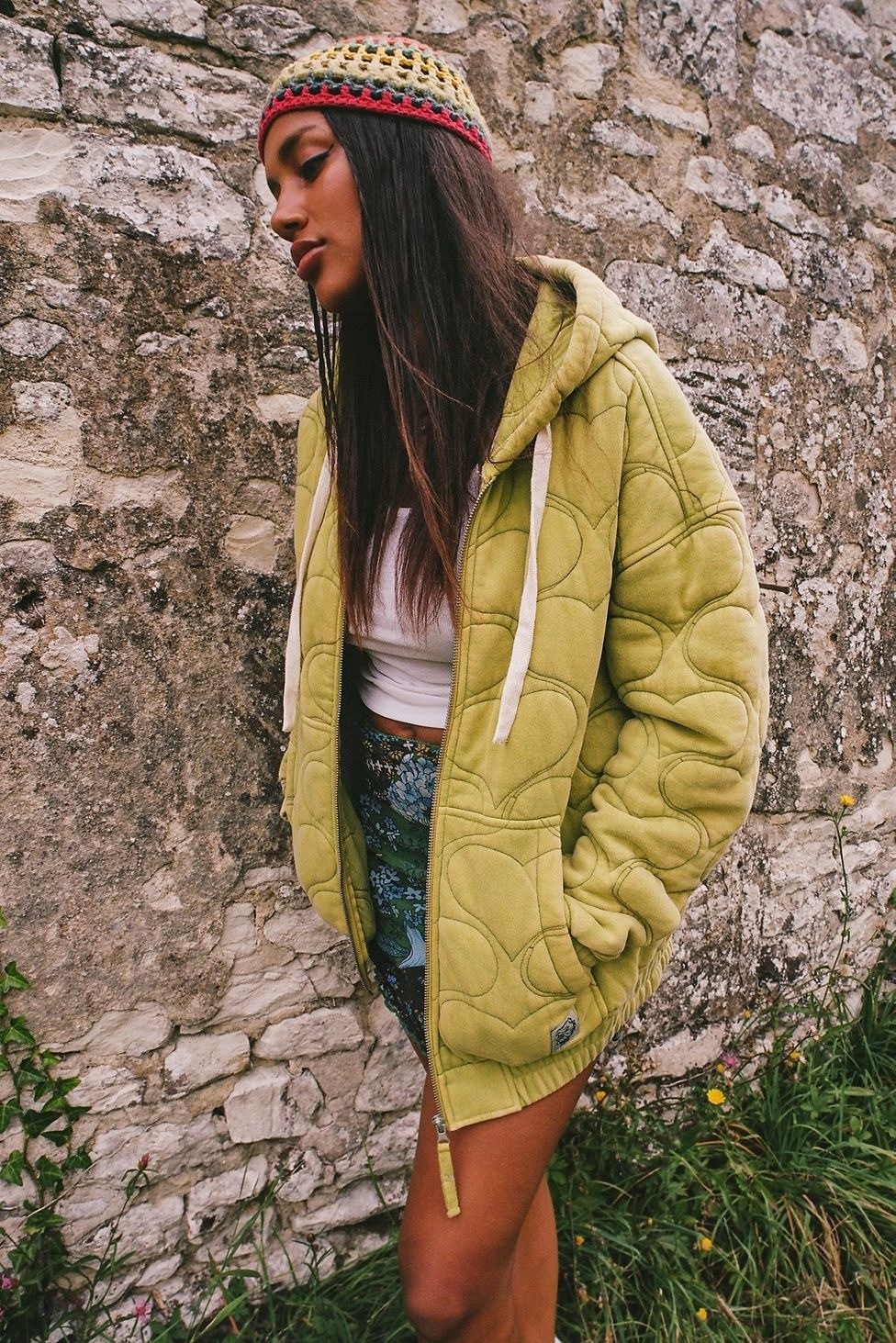 a model wearing the green embroidered sweatshirt outside
