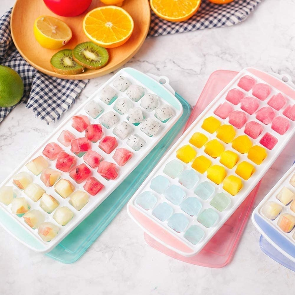 teal and pink small-sized ice cube tray filled with frozen cubes of ice and fruit juice