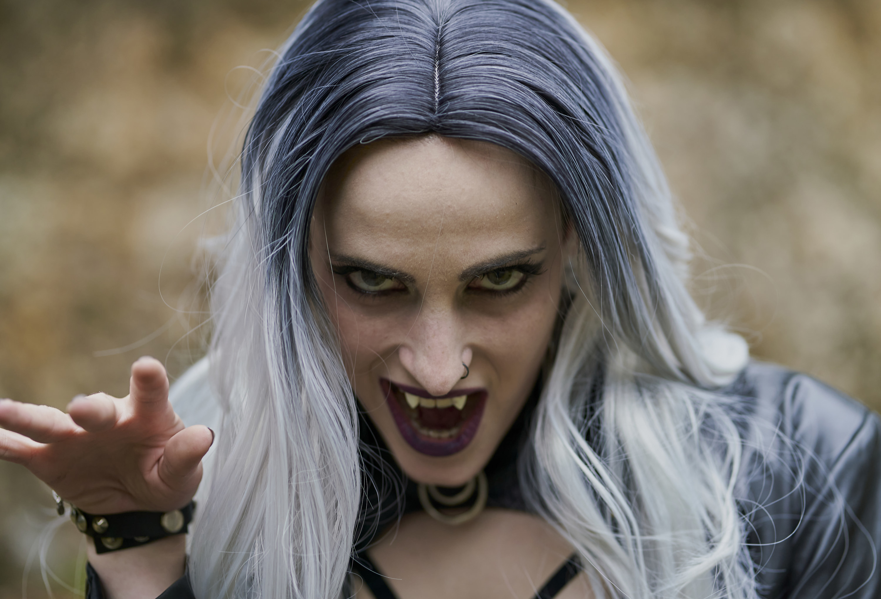 Portrait of woman in a vampire costume and opening her mouth to show the fangs