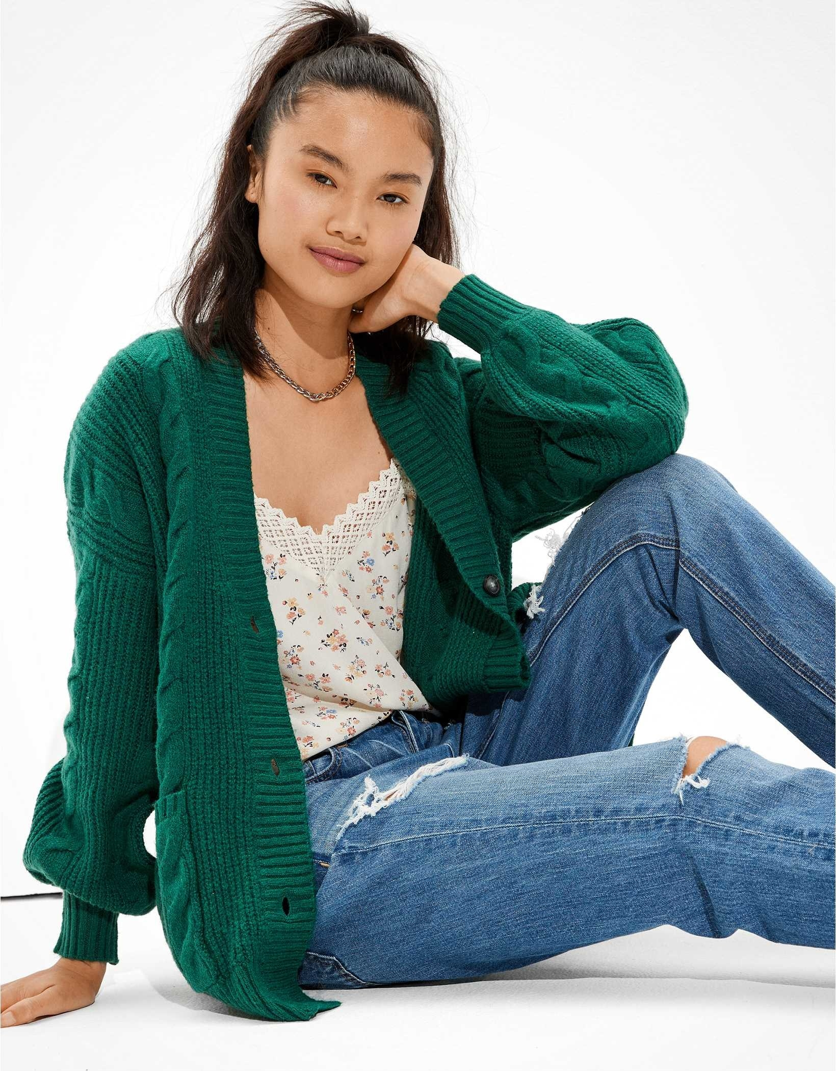 a model in an oversized green cardigan