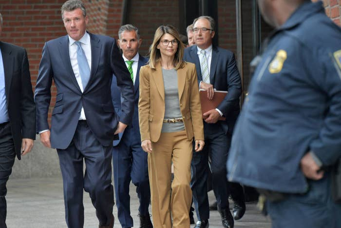 Lori and Mossimo walking outside of a courtroom with their lawyers