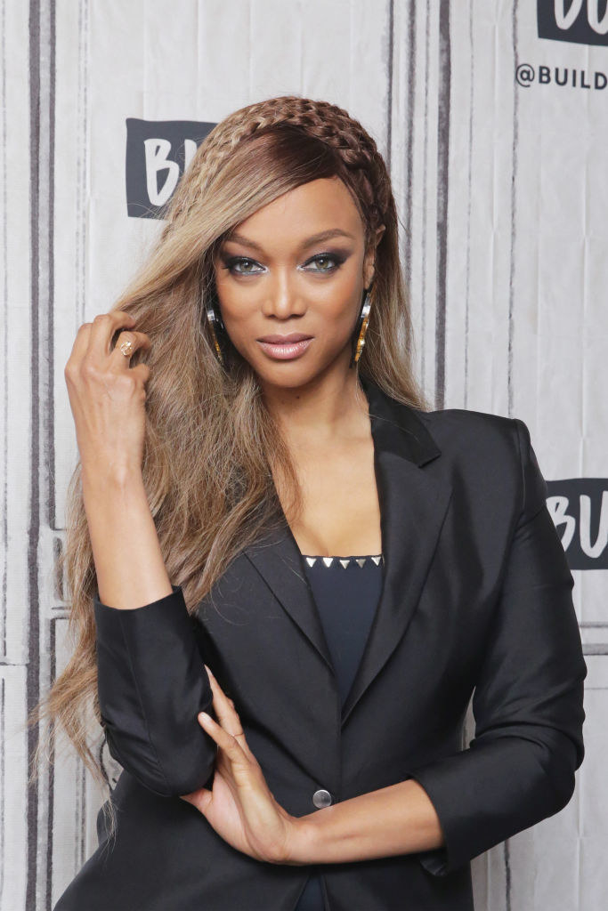 Tyra posing for a photoshoot in a pantsuit