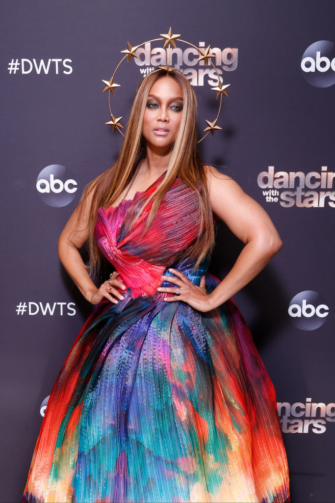 Tyra posing in a multicolored, one-shoulder dress with star headpiece at a Dancing with the Stars event