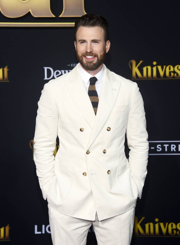 Chris Evans in a light-colored suit and a striped tie at the premiere of Knives Out