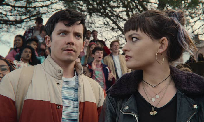 Emma Mackay standing next to Asa Butterfield and looking at him with a group of people behind them