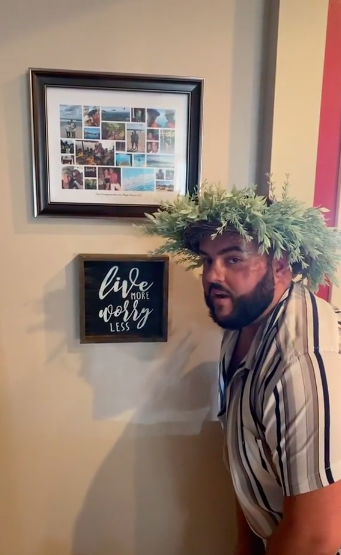 """Man wearing a wreath and standing next to a """"Live more worry less"""" sign on a wall below a framed montage of small photos"""