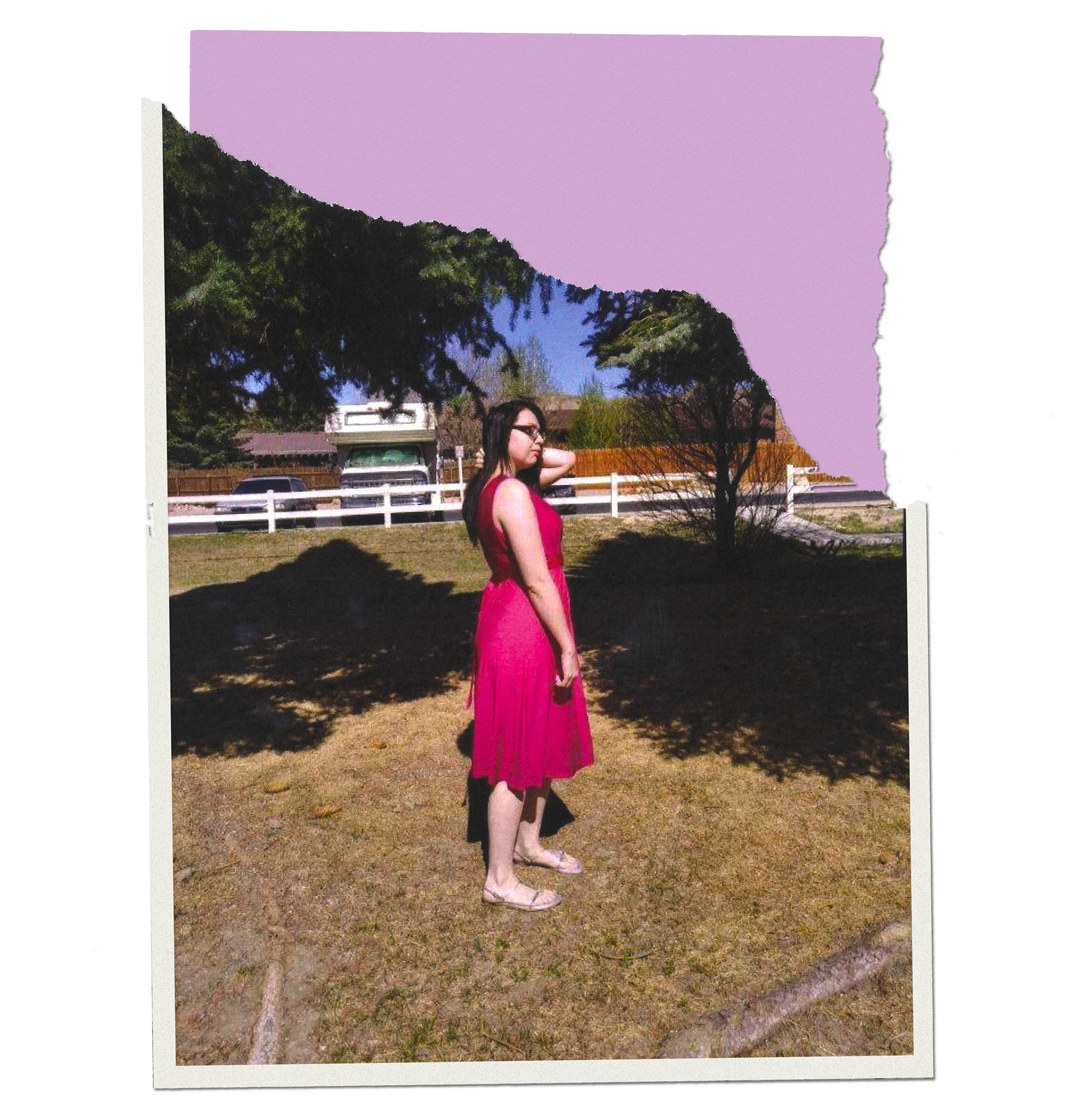 Arieana standing on grass in a dress and sandals and touching her hair