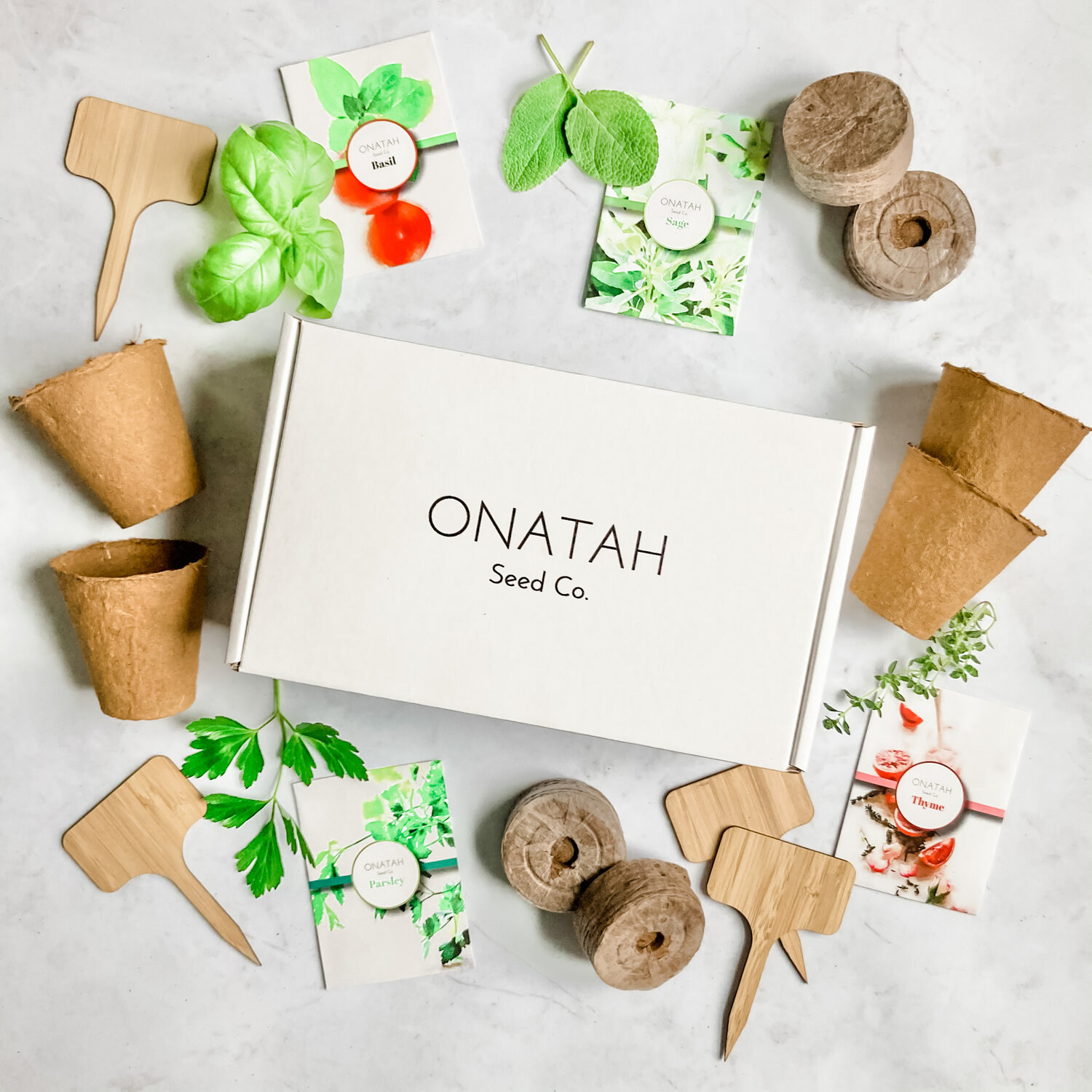 A white box that says Onatah Seed Co. on the front surrounded by garden tools