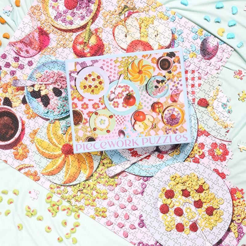 One-thousand piece colorful puzzle featuring a table filled with colorful breakfast cereal and fruit on tableware