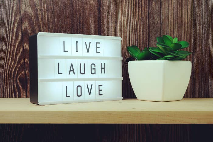 """""""Live Laugh Love"""" illuminated next to a plant on a shelf"""