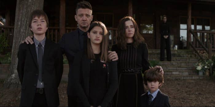 Hawkeye stands with his eldest son, middle daughter, and young son along with his wife at a funeral