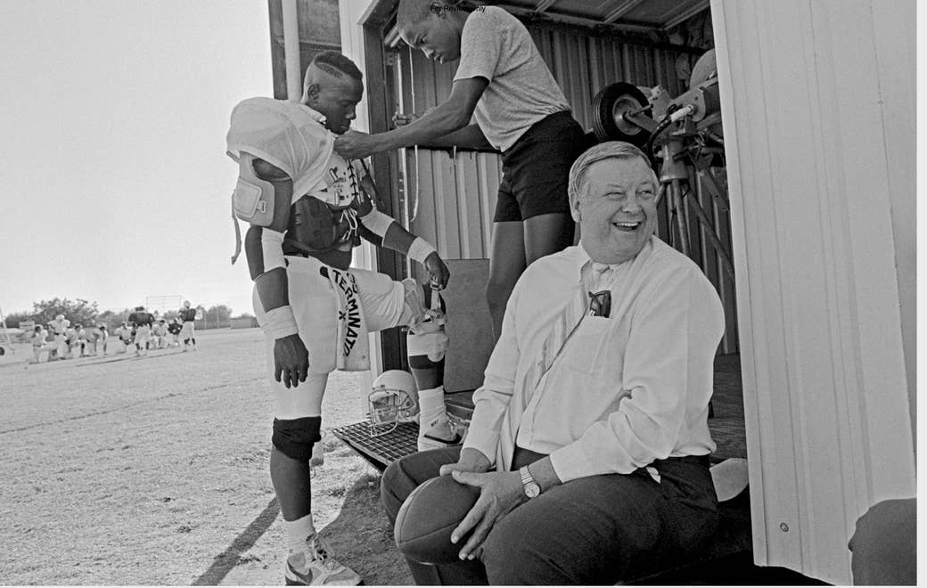 Black-and-white photo, with older sitting man laughing and player in uniform and another young man behind him